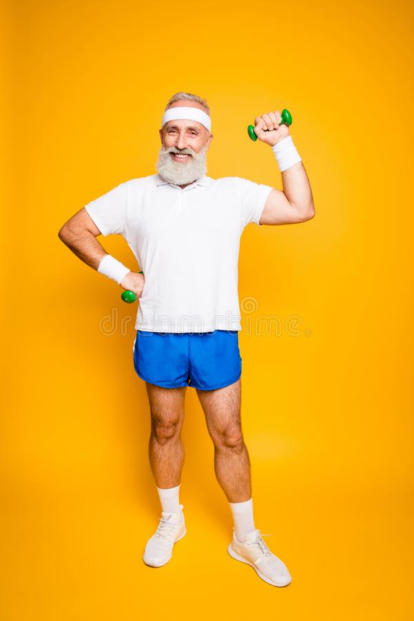 Full length of cheerful emotional cool grandpa with humor grimace exercising holding equipment, lifts it with strength and power. Body care, hobby, weight loss royalty free stock images