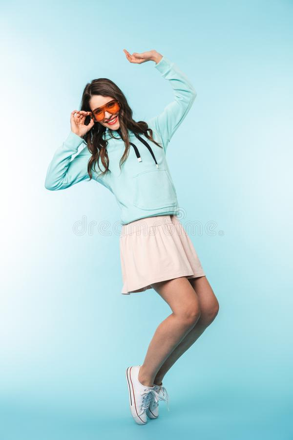 Full length of a cheerful young brunette woman standing stock photography