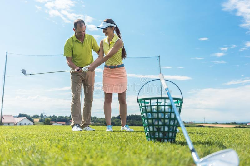 Cheerful young woman learning the correct grip and move for using the golf club. Full length of a cheerful young women learning the correct grip and move for royalty free stock photography