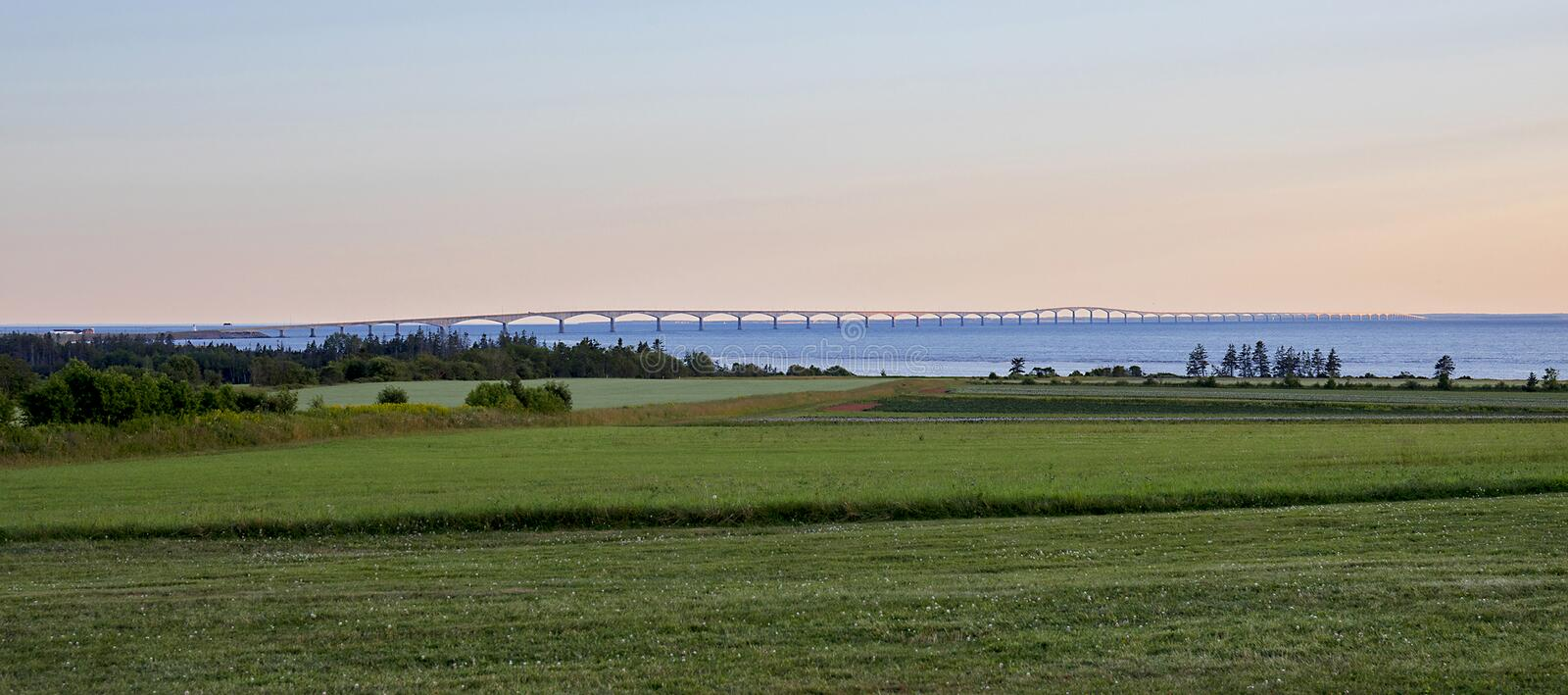 Full Length Confederation Bridge. The full length of the Confederation Bridge, seen in the distance from Prince Edward Island, Canada with agriculture fields in royalty free stock image