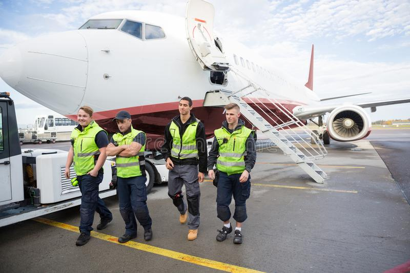 Confident Ground Crew Walking Against Airplane stock image