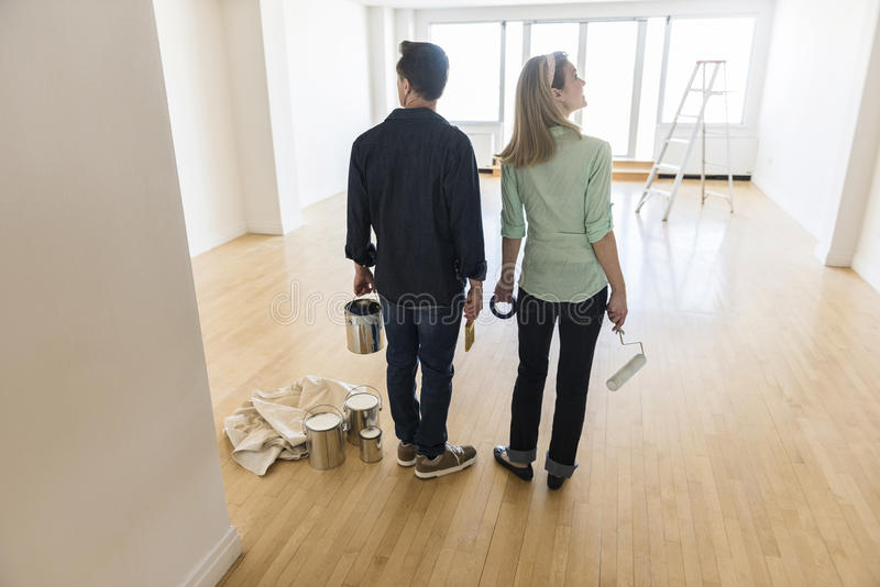 Full Length Of Couple With Paint Equipment At Home. Full length rear view of mature couple with paint equipment standing at home royalty free stock image