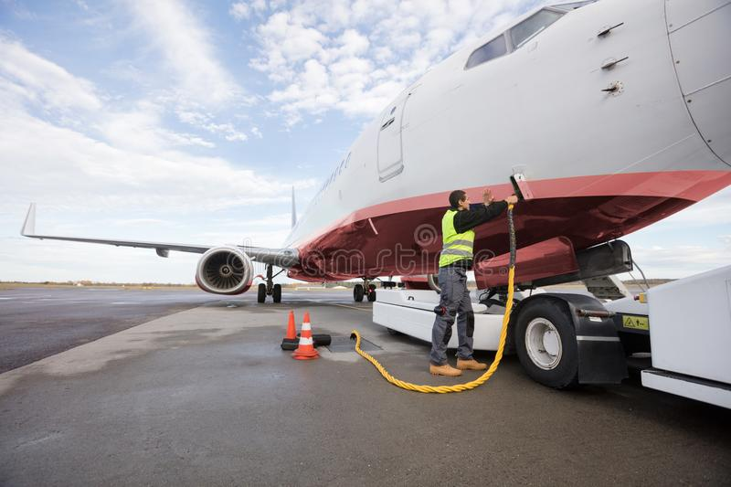 Full Length Of Crew Member Charging Airplane. On runway stock photos