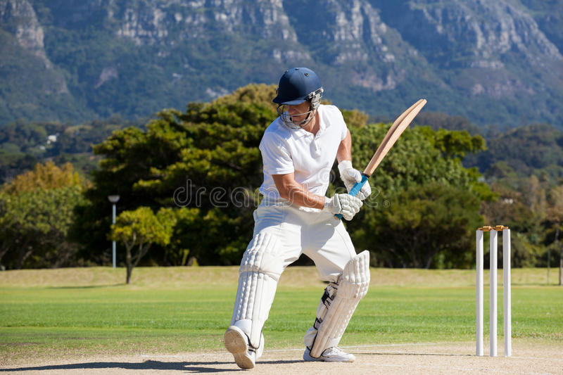 Full length of cricket player playing on field royalty free stock photo