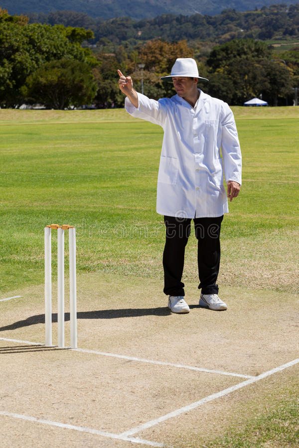 Full length of cricket umpire signalling out during match stock image