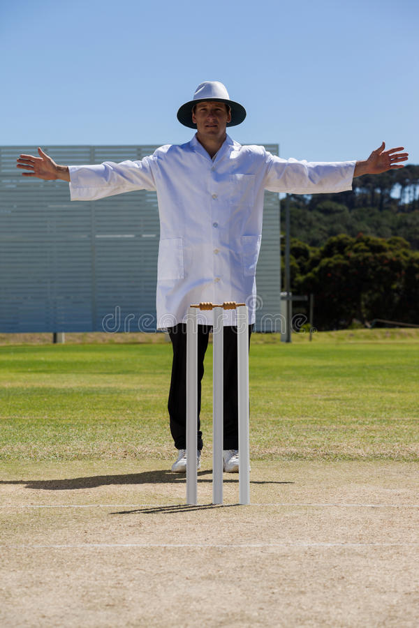 Full length of cricket umpire signalling wide ball during match royalty free stock photos