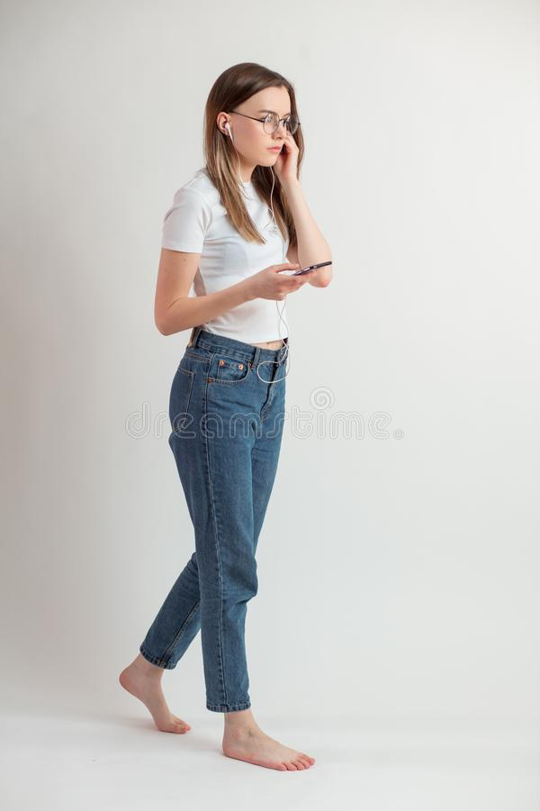 Full length side view portrait of young female studing with the smartphone royalty free stock photo