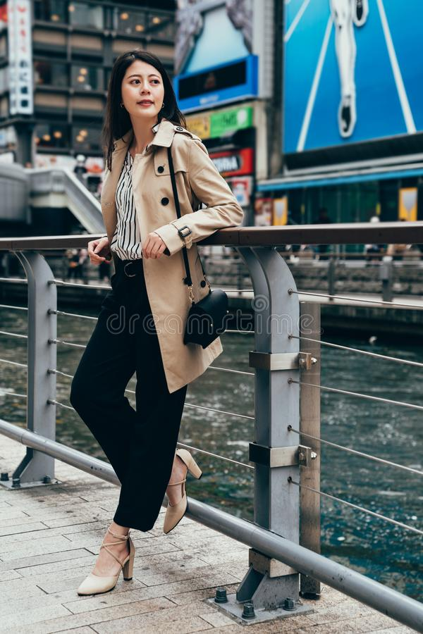 Female business worker after work near the river. Full length of fashion urban young woman living city lifestyle concept. female business worker after work stock image