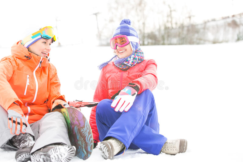 Full length of female friends with snowboard relaxing during winter stock images