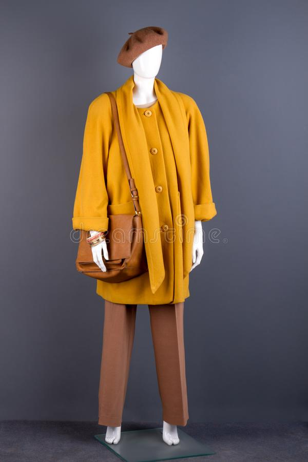 Full length female mannequin in fashion outfit. Ladies modern topcoat, handbag and headgear. Women stylish clothes and accessories stock photography