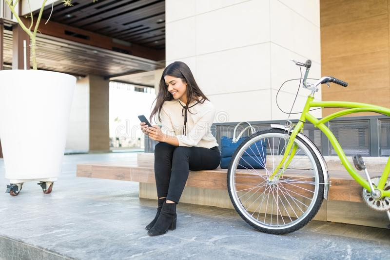 Female Manager Holding Smartphone By Cycle stock photos