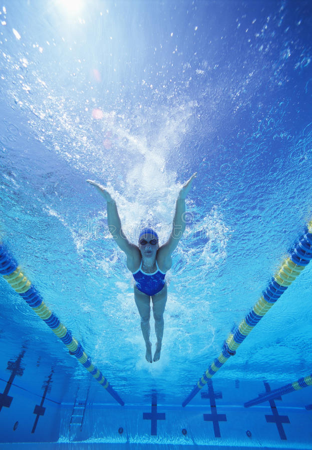 Full length of female swimmer in United States swimsuit swimming in pool royalty free stock photos