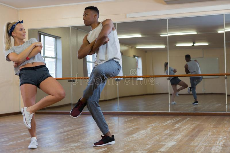 Full length of friends practicing dance against mirror. On floor at studio royalty free stock photo
