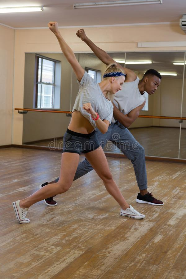 Full length of friends rehearsing dance against mirror. On floor at studio royalty free stock image