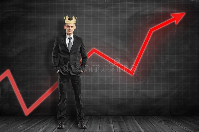 Full length front view of businessman wearing crown, standing hands in pockets, with red graph arrow going up behind him royalty free stock photography