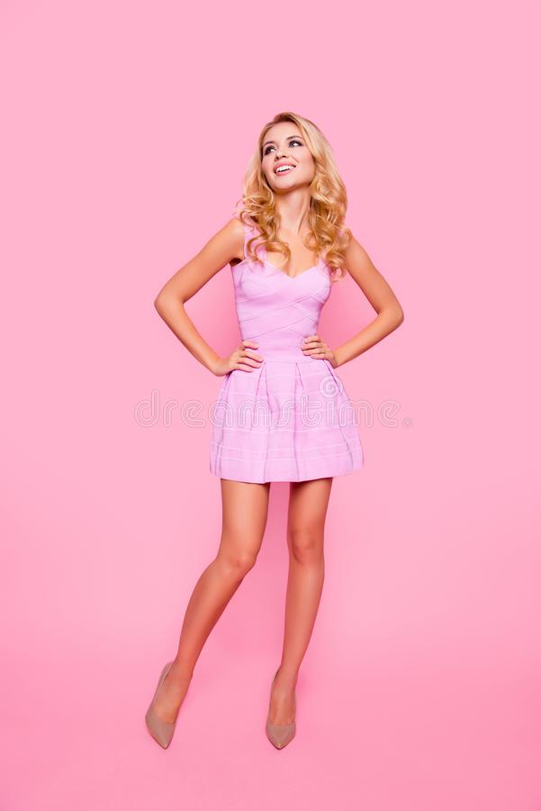Full length front view portrait of attractive, caucasian, cute, positive girl in cocktail dress, holding her hands on waist, look stock image