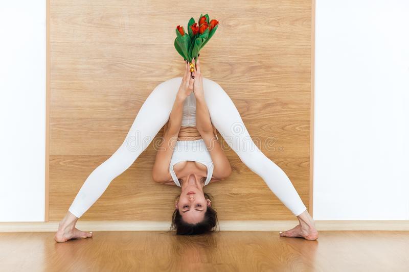 Full-length front view of sporty young woman in a white suit practicing yoga doing standing straddle forward bend pose, Prasarita stock photo