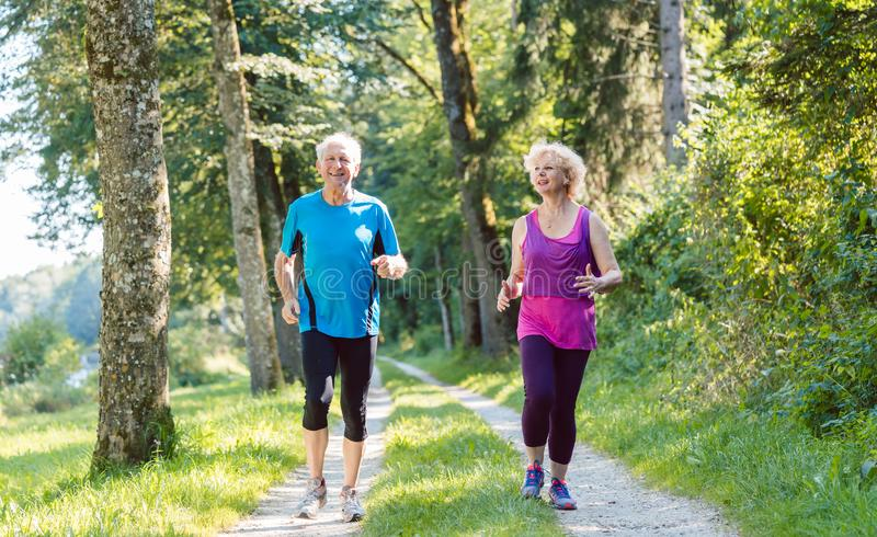 Two active seniors with a healthy lifestyle smiling while joggin stock image