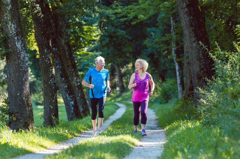 Two active seniors with a healthy lifestyle smiling while joggin. Full length front view of two active seniors with a healthy lifestyle smiling while jogging royalty free stock image