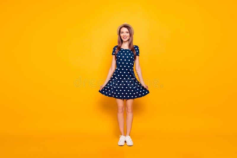 Full-length, fullbody portrait of nice, cheerful, positive, childish, comic, funny, cute girl, holding bottom of polka-dot dress stock photography
