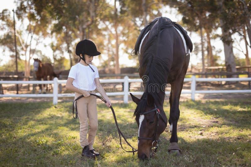 Full length of girl wearing helmet standing by horse stock photo