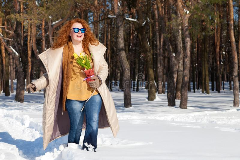 Full length of glamour woman with bouquet of yellow narcissus walking through forest during day time royalty free stock photos