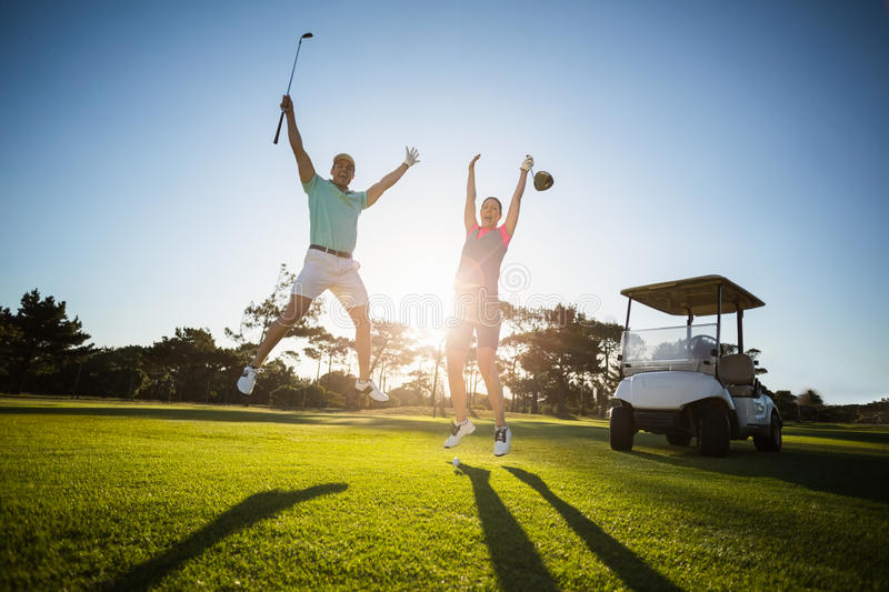 Full length of golf player couple with arms raised stock images