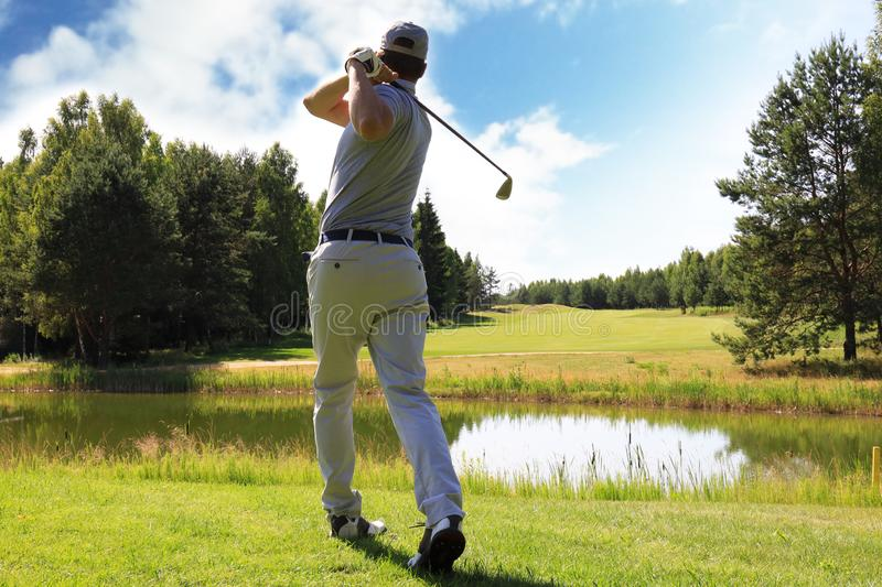 Full length of golf player playing golf on sunny day. Professional male golfer taking shot on golf course.  royalty free stock images