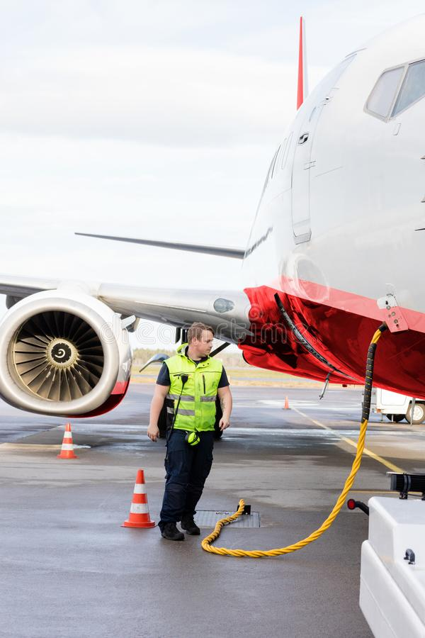 Ground Crew Member Walking By Airplane Being Charged On Runway. Full length of ground crew member walking by airplane being charged on runway royalty free stock photo