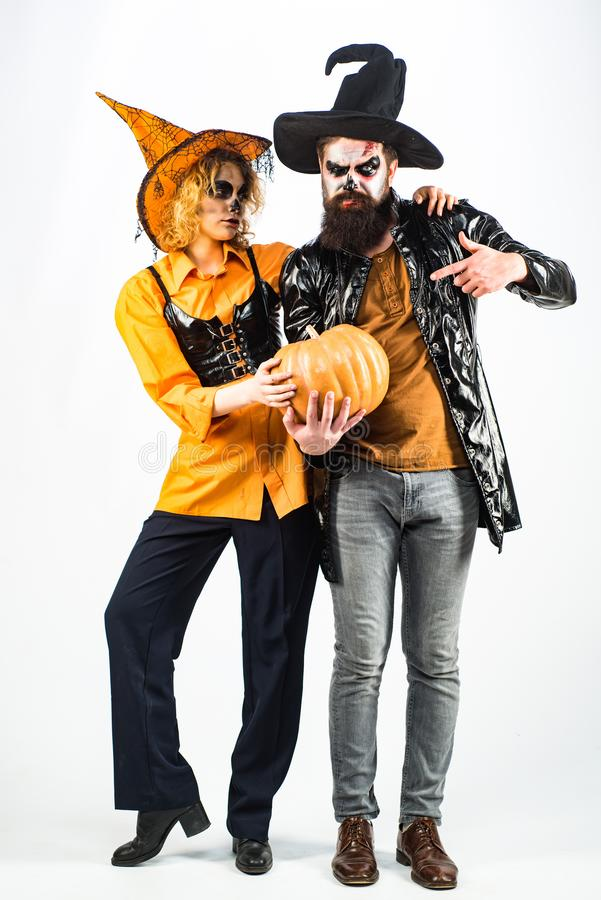 Full length Halloween Party couple. Two emotional young women and man in Halloween costumes on Halloween party with stock photos