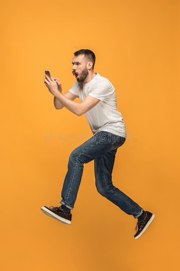 Full length of handsome young man taking selfie while jumping. Always on mobile. Full length of handsome young man taking phone while jumping against orange stock photos