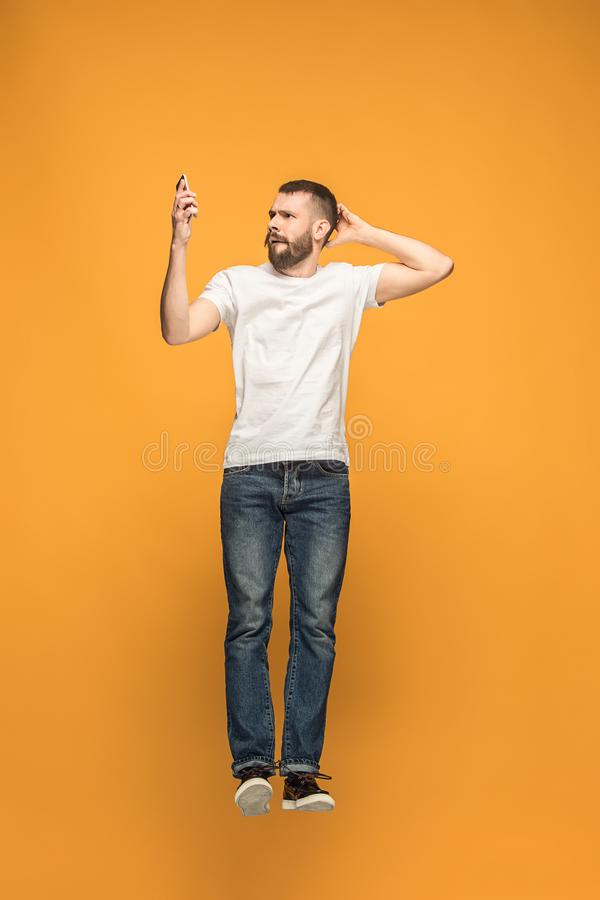 Full length of handsome young man taking selfie while jumping stock photography