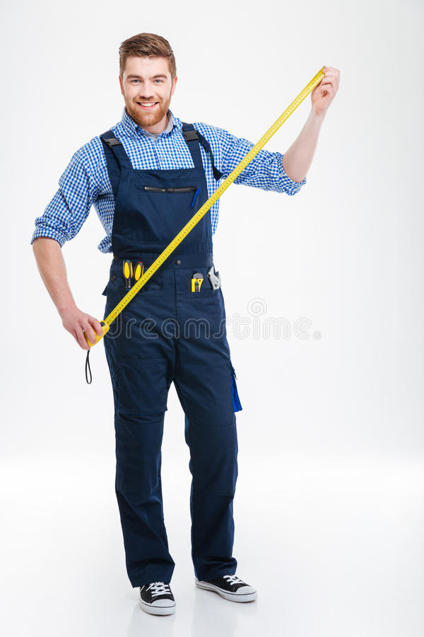 Full length of happy bearded young worker holding masuring tape royalty free stock photography