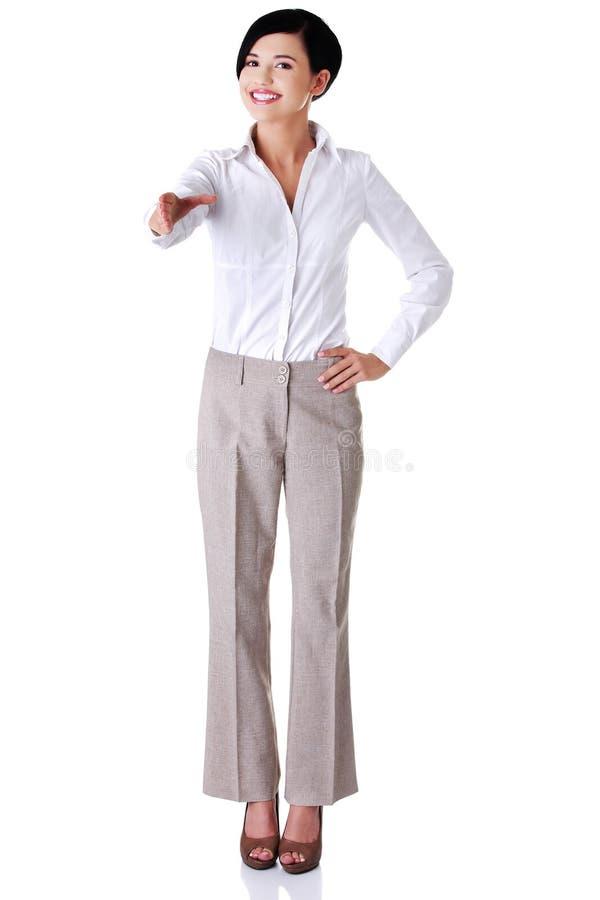 Full length happy businesswoman ready to handshake stock photography