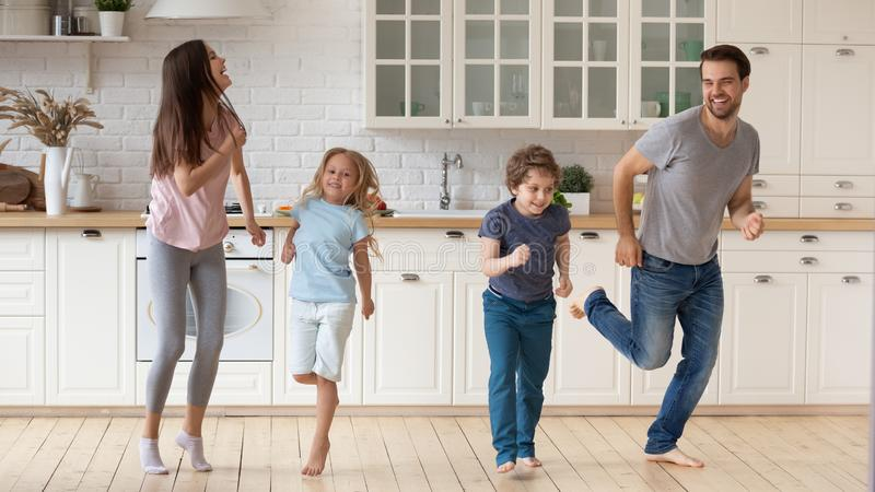 Full length happy family having fun together at modern kitchen. royalty free stock image