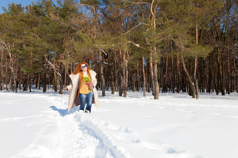 Full length of happy pretty woman going through snowy forest royalty free stock photos