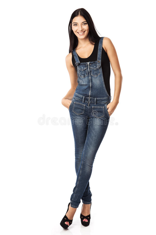 Full length of a happy young woman standing with hands in pockets royalty free stock photography