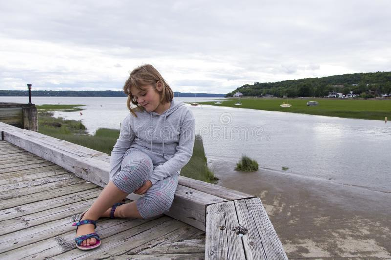 Full length horizontal shot of pretty fair little girl sitting on wooden pier with dreamy expression. Cap-Rouge waterfront, Quebec City, Quebec, Canada royalty free stock photo