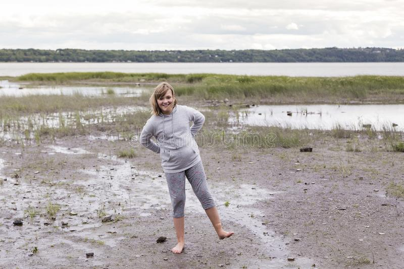 Full length horizontal shot of pretty smiling young girl standing on one foot on muddy beach. At low tide with cheeky expression, Cap-Rouge waterfront, Quebec royalty free stock photos