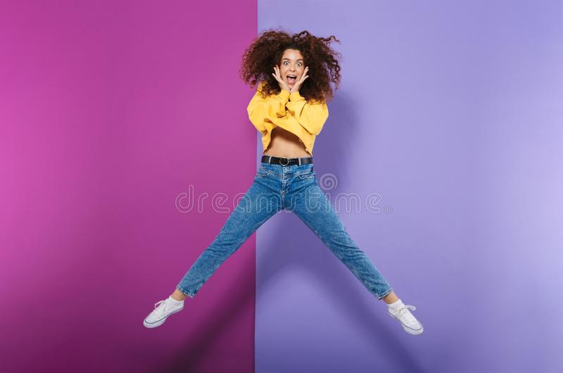 Full length image of amazed happy curly woman swearing casual clothes smiling and jumping stock photo