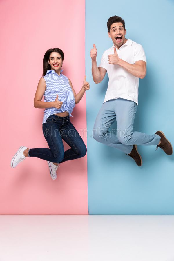 Full length image of cheerful man and woman in casual wear jumping and smiling together, isolated over colorful background royalty free stock photo