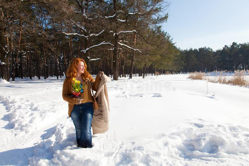 Full length of joyful pretty woman looking sideways and holding her coat in hand with snowy trees on the background royalty free stock images