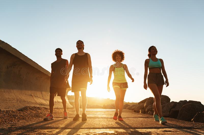 Full length image of fitness people walking outdoors. At the beach stock photography