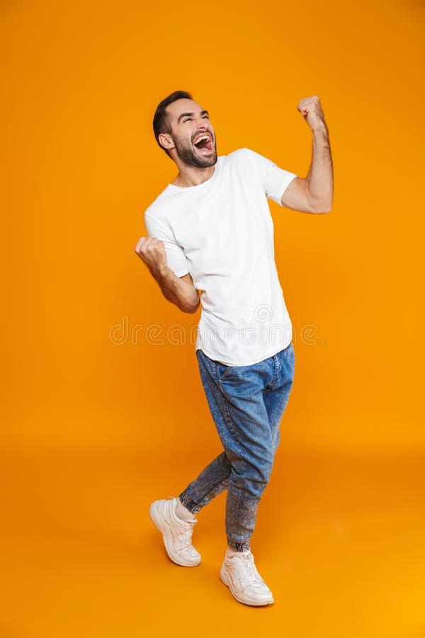 Full length image of good-looking guy 30s in t-shirt and jeans clenching fists while standing,  over yellow background stock photography