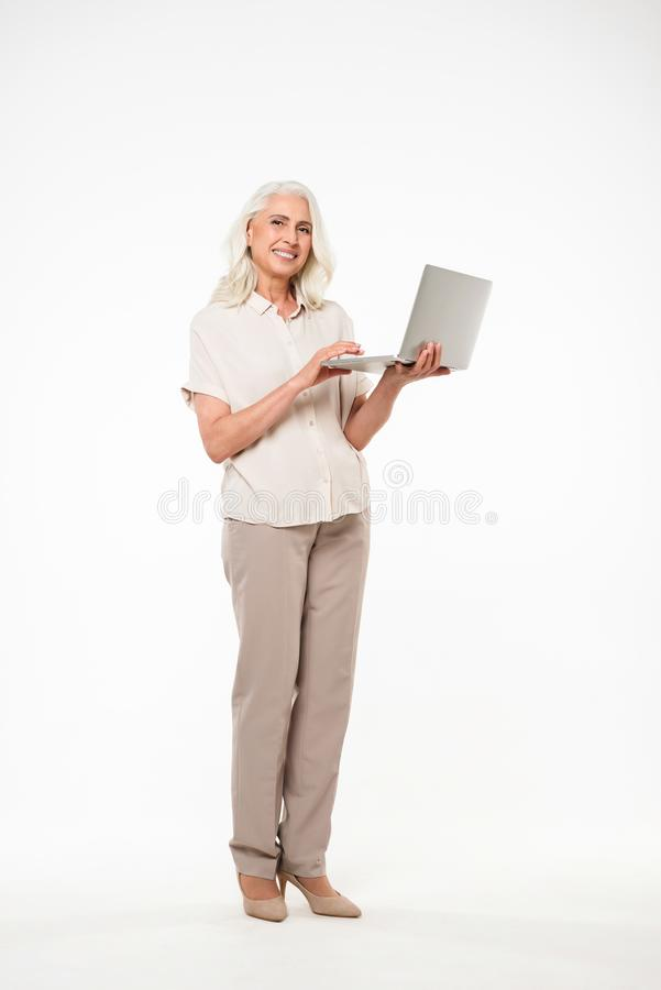 Full length image of mature adult granny 60s with gray hair smiling and holding silver laptop in hand, isolated over white stock photos