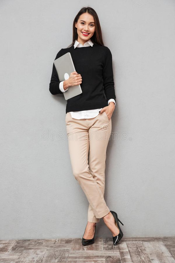 Full length image of Pleased asian woman in business clothes stock images