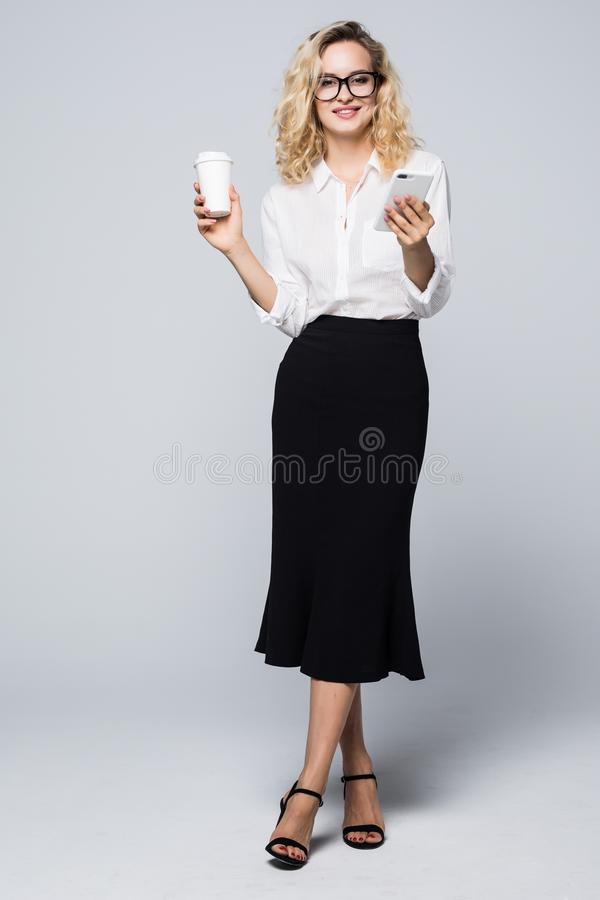Full length image of pretty business woman in formal wear standing and using cell phone with takeaway coffee in hand over gray bac stock photography