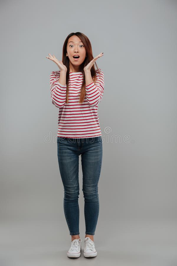 Full length image of shocked asian woman in sweater stock photos