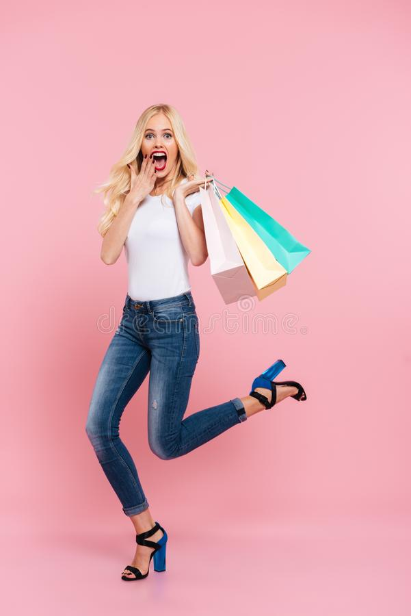 Full length image of shocked blonde woman moving with packages royalty free stock photo