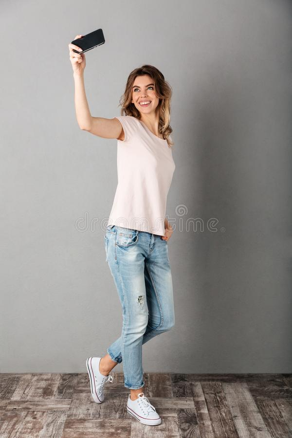 Full length image of Smiling woman in t-shirt making selfie stock photography